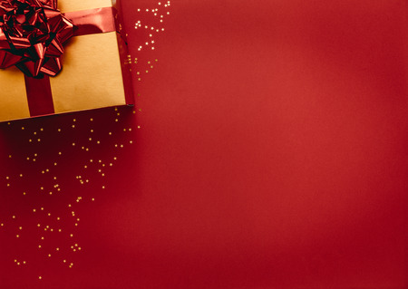 Golden coloured gift box with stars on red background. Top view of christmas gift with stars flat lay on red background.