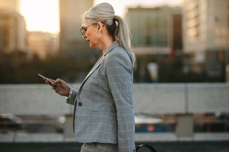 Side view of senior businesswoman reading text message on her smart phone while walking outdoors. Mature woman reading messages on a smartphone while walking on urban background.
