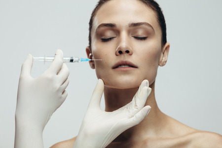 Close up of female face getting injected by syringe. Beautiful woman gets injection in her face by a beautician wearing hand gloves. Stok Fotoğraf