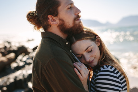 Affectionate couple embracing outdoors on beach. Beautiful woman being embraced by her loving boyfriend on the beach.