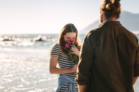 Beautiful woman smelling flowers on beach with boyfriend. Woman loving the surprise given by her boyfriend. Loving couple in beach.