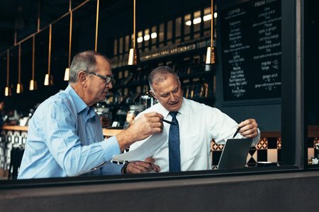 Mature business people looking at laptop and discussing work at cafe. Two business partners meeting in a restaurant. Stock Photo