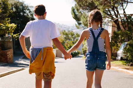 Kids in love walking on a street hand in hand on a sunny day. Boy and girl walking on a deserted road together.