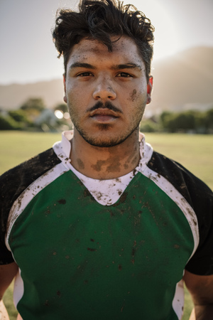 Young sportsman looking at camera while standing on ground. Close up portrait of young rugby player smeared in mud. Imagens