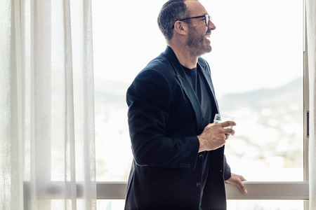 Handsome mature businessman looking outside the window and drinking whisky. Mid adult man in suit with a glass in drink in hand standing at hotel room window and smiling.