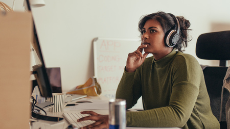 Young woman working on computer in tech startup office. Female programmer sitting at desk and looking away thinking. Stock Photo