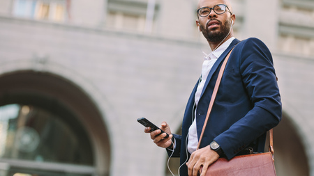 Low angle view of young african businessman with bag walking outdoor on street listening to music from mobile phone. Handsome businessman using smartphone for listening music while walking on city street. Standard-Bild