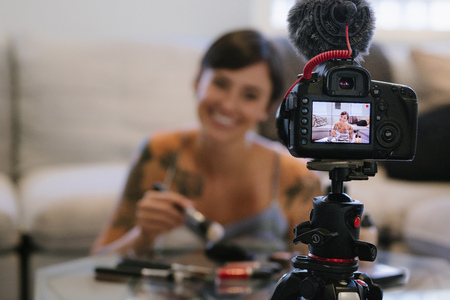 Young female  recording  video on camera with makeup cosmetic at home. Focus on tripod mounted camera screen showing female fashion  reviewing make up products.