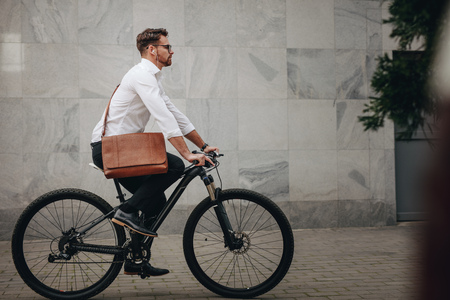 Side view of a man wearing an office bag riding a bike. Businessman going to office on a bicycle listening to music. Stock Photo