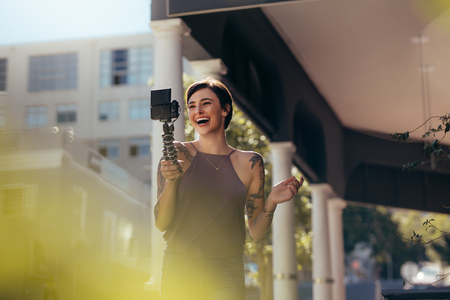Young caucasian female  laughing while making a video outdoors in city. Social media influencer recording content for her video blog.