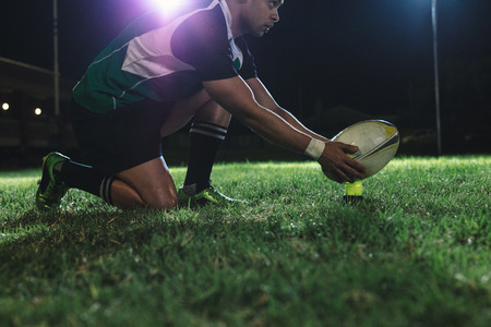 Rugby player placing the ball on tee for penalty shot during the game. Rugby player making a penalty shot under lights at sports arena. Stockfoto