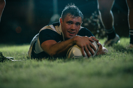 Rugby player scores a touchdown during the game. Rugby player making a touch down during the match. Imagens