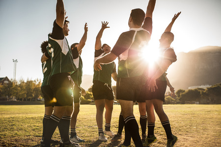 Rugby players celebrating a win at the sports field. Rugby team with hands raised and screaming after victory.
