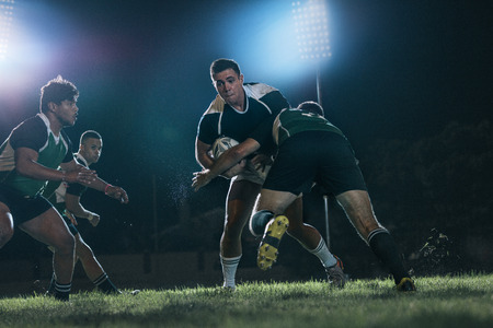 Strong rugby players fighting for the ball during the game. Intense rugby action under lights at sports arena.