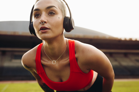 Fitness woman training in a stadium bending forward with hands on knees. Female athlete doing workout wearing wireless headphones. Archivio Fotografico