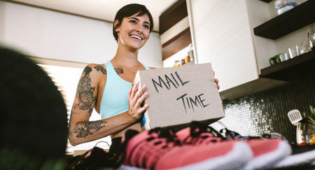 Smiling young woman looking at camera with fan mail box in hand. Female vlogger making mail time video at home Banco de Imagens
