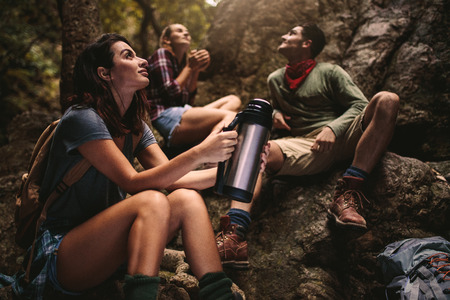 Woman sitting on rocks holding thermal bottle with friends sitting at the back in forest. Group of friends taking a break while hiking in nature.