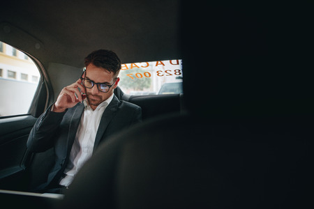 Businessman managing office work on the move sitting in a cab. Entrepreneur talking over cell phone and looking at office files while commuting to office in a taxi.