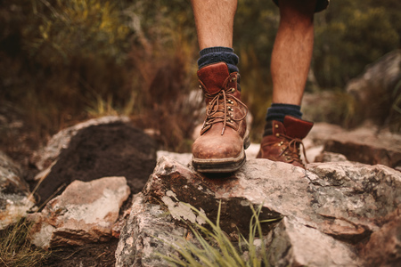 Closeup of male hikers shoes on rocky trail. Man walking through rugged path wearing trekking boots.