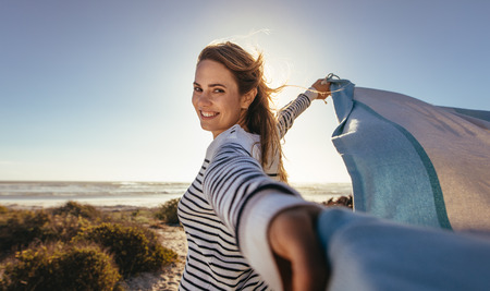 Portrait of a smiling woman holding a drape against the sea breeze. Woman standing at the beach holding a flying cloth with both hands. Reklamní fotografie