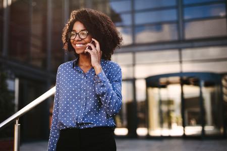 Positieve afrikaanse vrouw in formele kleding die buiten loopt en praat op een slimme telefoon. Vrouwelijke zakelijke professional die een telefoongesprek voert terwijl ze buiten loopt met een gebouw op de achtergrond.