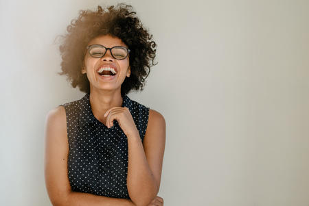 Portrait of excited young woman standing by a wall and laughing. Cheerful young african female with curly hair and spectacles. Stockfoto