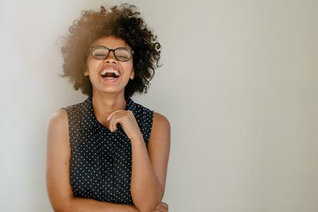 Retrato de mujer joven emocionada de pie junto a una pared y riendo. Alegre joven africana con pelo rizado y gafas.