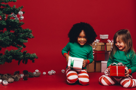 Happy kids playing with their christmas gifts sitting on floor. Multi ethnic kids holding their christmas gifts sitting beside a christmas tree. 스톡 콘텐츠
