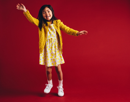 Cheerful girl waving her hand standing against a red background. Smiling asian kid playing.