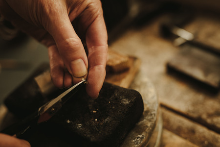 Hands of female jeweler cutting small pieces of metal for making jewelry. Jewelry designer working at her workbench.