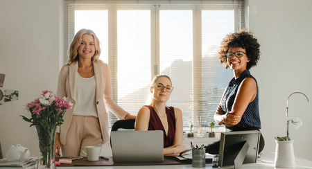 Three businesswomen in casuals at desk looking at camera and smiling. Successful startup business partners in office. Stock Photo