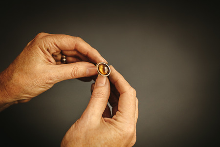 Close up of female jewelry maker hands examining silver ring with gem stone against grey background. Jeweler inspecting ring.
