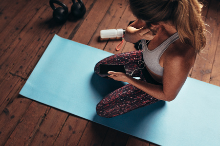 Top view of young woman sitting on yoga mat wearing earphones to listen music on mobile phone after workout. Fitness woman at gym listening to music during break.