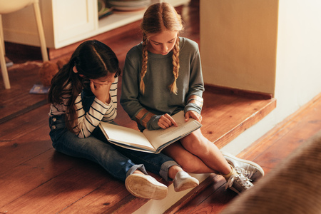 Girl reading storybook for her little sister. Two girls sitting on floor reading a book at home. Stock Photo