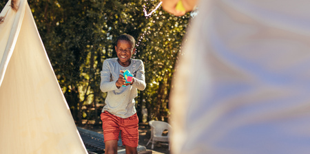 Little african boy playing squirt gun fight with friend in backyard. Kids enjoying playing water gun fight outdoors. Stock Photo