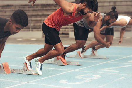 Runners using starting blocks to start the race on running track. Athletes starting their sprint on a running track with the help of starting blocks.