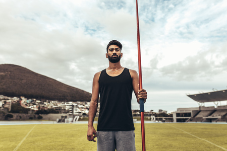 Athlete standing in a track and field stadium holding a javelin. Athlete training in javelin throw standing in a ground. 免版税图像