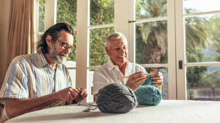Old men sitting at home and knitting sweater with the knitting needles and woolen threads. Senior people learning knitting at retired age.