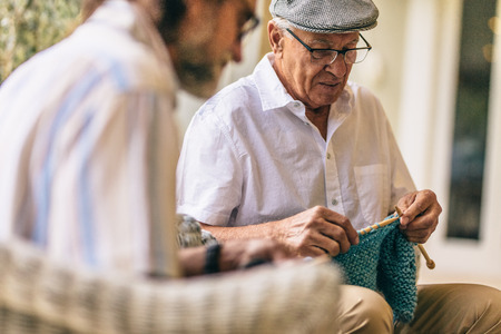 Two old men sitting knitting warm clothes. Senior friends sitting on chairs and kitting woollen wear with knitting needles and wool yarn. Stockfoto - 116021802