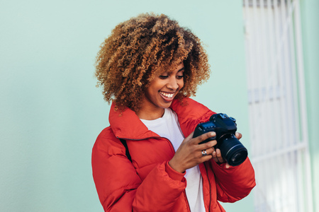Cheerful afro american woman on vacation taking photos standing outdoors. Portrait of a tourist woman looking at her dslr camera after taking a photo.