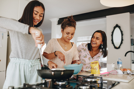 Young girls preparing breakfast in kitchen. Smiling girl cooking food while her friends help her in kitchen.
