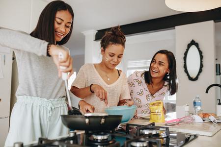 Jonge meisjes bereiden ontbijt in de keuken. Glimlachend meisje dat eten kookt terwijl haar vrienden haar in de keuken helpen.