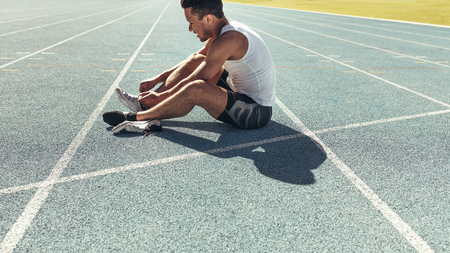 Athlete sitting on a running track tying shoe lace. Runner sitting on the running track wearing his shoes.