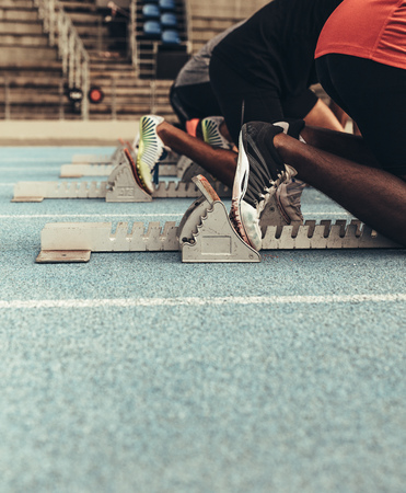 Sprinters on their mark ready to sprint on an all weather running track. Runners using a starting block to start their run on the race track. Stockfoto