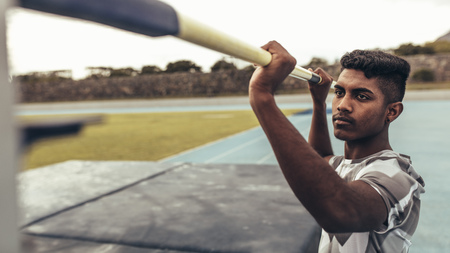 Man setting up a pole at a height for high jump. Close up of a man resetting the height of the bar for high jump.