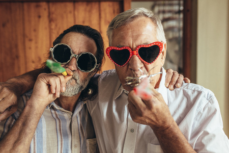 Two old friends with party blowers. Senior men wearing funny sunglasses blowing party whistles indoors.
