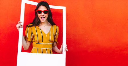 Excited girl standing against red wall holding a empty picture frame. Beautiful woman in sunglasses looking through blank photo frame. Фото со стока