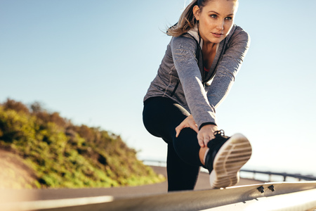 Woman athlete doing stretching exercises on the side railing of a road. Woman in fitness wear bending forward stretching her leg on a roadside railing. 版權商用圖片