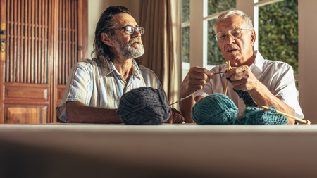 Senior man doing knitting with his friends looking on. Active seniors knitting with needles and wool yarn.