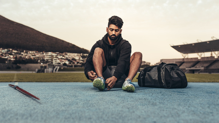 Athlete getting ready for training wearing shoes sitting in a track and field stadium. Man tying shoe lace sitting on track with a javelin and bag by his side. Stockfoto